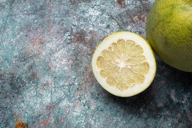 Нарезанный пополам свежий грейпфрут на темном фоне