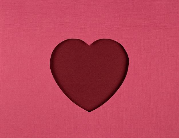赤い背景に切り絵のハート、紙はアートスタイルを切り取った。バレンタインデーカード、切り絵。フラットレイ、上面図、コピースペース。バレンタインデーペーパーアート
