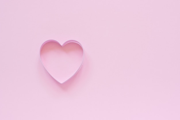 Cutter cookies in heart shape on pastel pink background