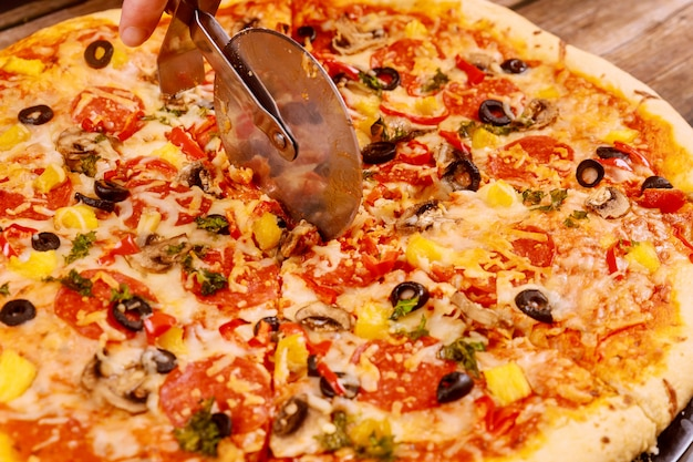 Cutter cut round supreme pizza, close up.