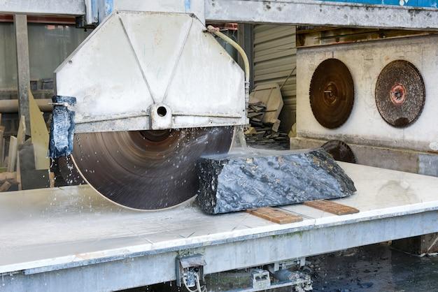 작업대에 있는 돌을 가까이서 물로 냉각시킨 대형 원형 동력 톱을 사용하여 작업장에서 블랙 포르토로 이탈리아 대리석 블록을 절단