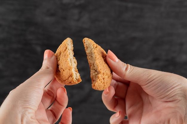 손에 든 오트밀 쿠키를 두 조각으로 자릅니다.