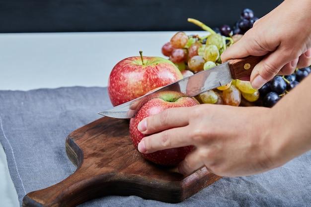 Tagliare una mela sul tagliere della frutta con l'uva intorno.