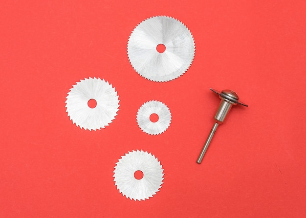 Cutting blades for professional engraving machine isolated on red color, dremel attachments