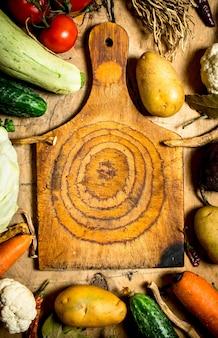 Разделочная доска и ингредиенты для приготовления супа на деревянном столе.