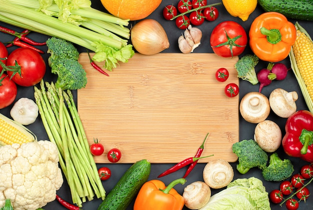 Разделочная доска и много разных овощей для приготовления
