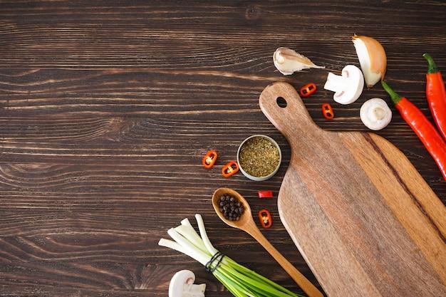 木製のテーブルの背景、テキストの場所で調理するためのまな板と野菜。上面図。