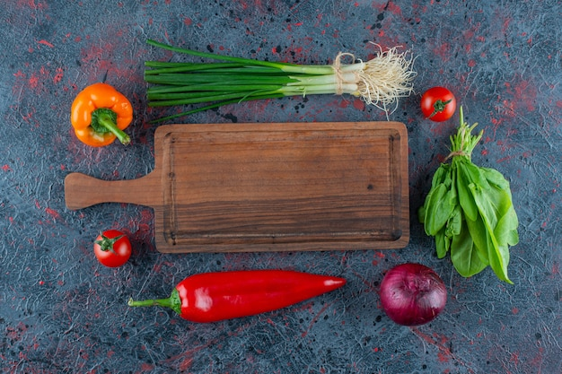 大理石の背景にまな板と野菜。