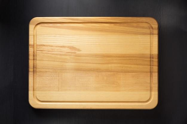 Разделочная доска на поверхности деревянного стола