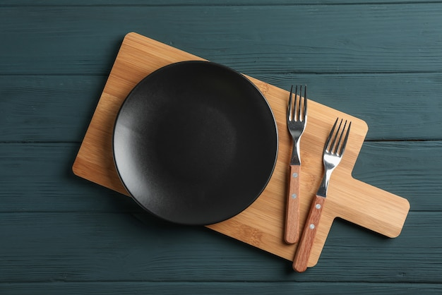 Cutting board and cutlery on wooden background, space for text