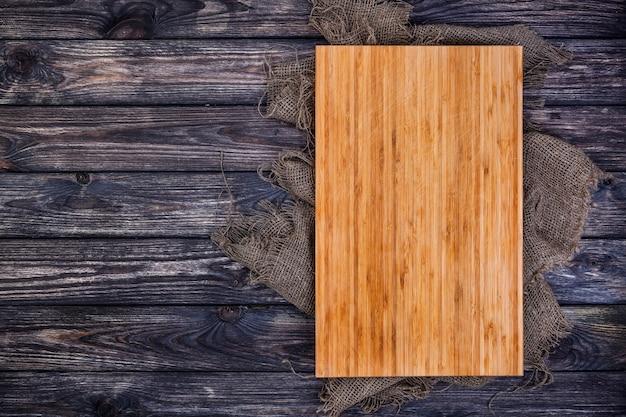 Cutting board on dark wood, top view