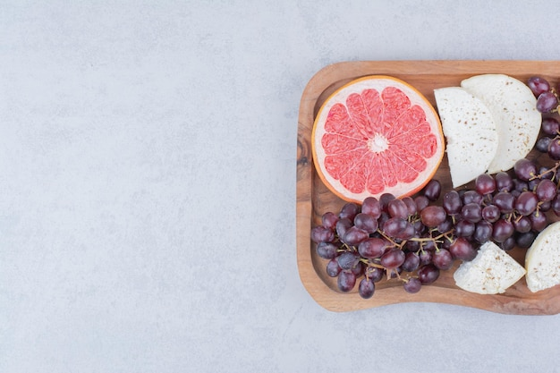 A cutting board full of cheese, slice of grapefruit and grapes. high quality photo