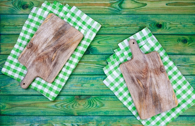Cutting board over green checkered tablecloth, top view