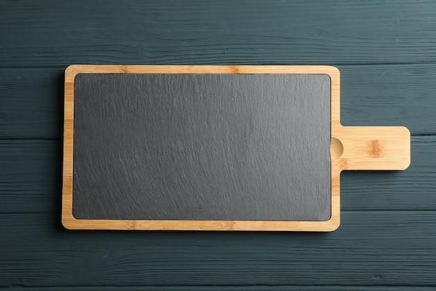 Разделочная доска на деревянном фоне, место для текста