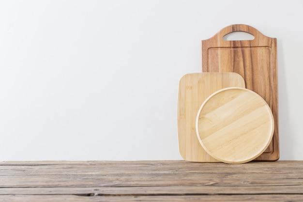 Разделочная доска на деревянном столе на фоне белой стены
