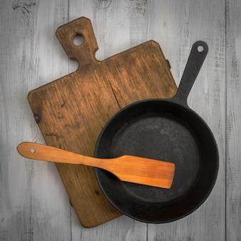 Cutting board, pan and wooden spatula