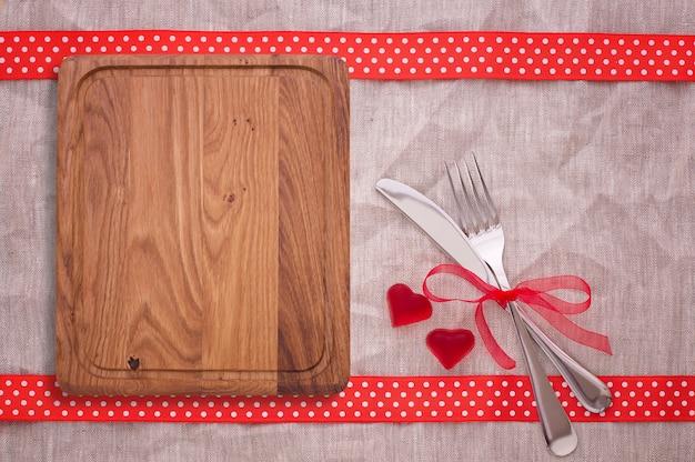 Разделочная доска, красные сердечки и столовые приборы на холщовой скатерти