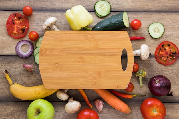 Cutting board surrounded by different fruits and vegetables