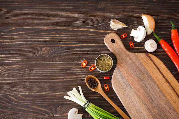 Cutting board and vegetables for cooking on wooden table background, place for text. top view.