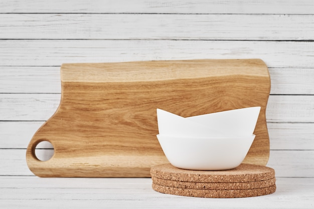 Cutting board and white ceramic cup on white