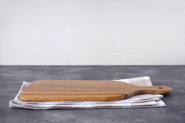 Разделочная доска с кухонным полотенцем на сером фоне, место для текста.