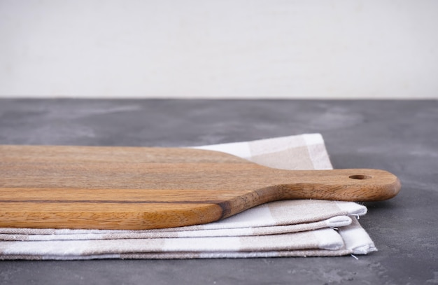 Разделочная доска с кухонным полотенцем на сером фоне, место для текста, крупный план.