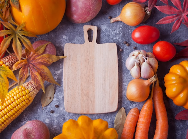 Cutting board with autumn leaves and vegetables on the black background