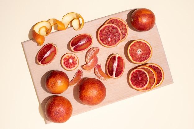 Разделочная доска с дольками кровавого апельсина и целыми цитрусовыми на желтом