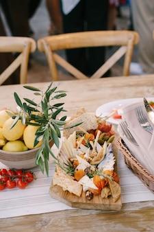 Разделочная доска с сырами, солеными огурцами и инжиром на столе с тарелкой лимонов и помидоров черри