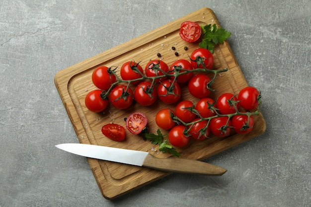 회색 질감 배경에 체리 토마토와 칼 커팅 보드
