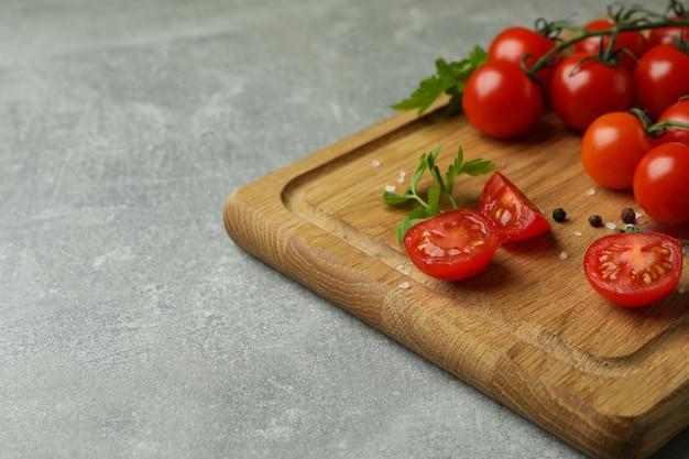 회색 질감 배경에 체리 토마토와 보드 절단