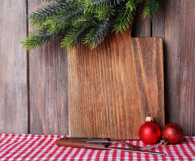木の板の背景にクリスマスの装飾とまな板