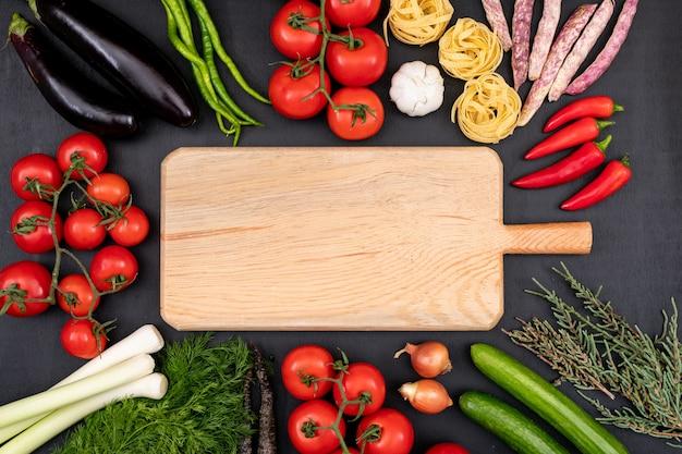 Разделочная доска с копией пространства в окружении овощей