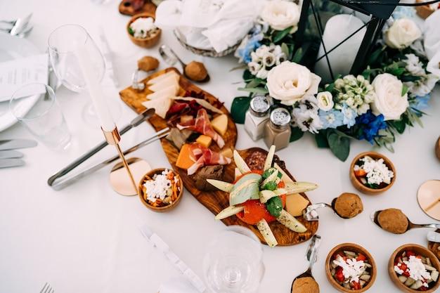 Разделочная доска с деликатесами на столе с чашами солонка, шейкер и большая свеча