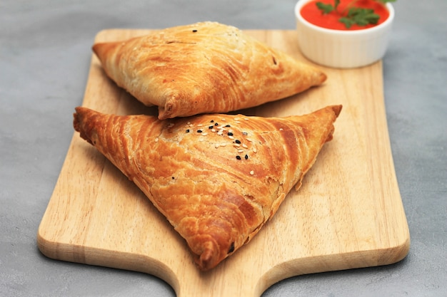 Cutting board with delicious meat samosas and red sauce on gray