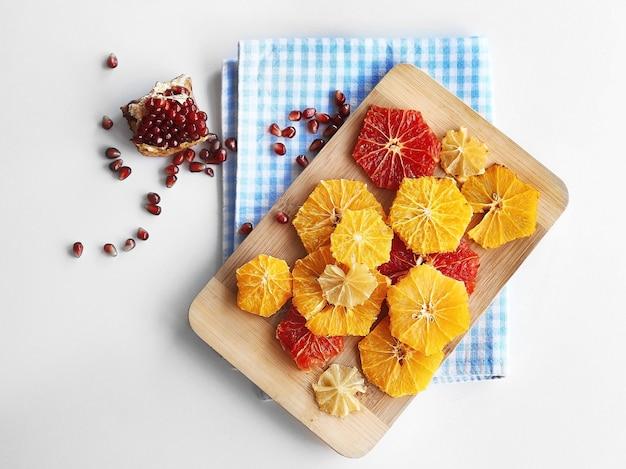 明るい表面に異なる柑橘類のスライスを持つまな板