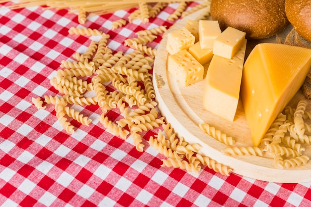 Cutting board with fresh cheese near bread and scattered pasta