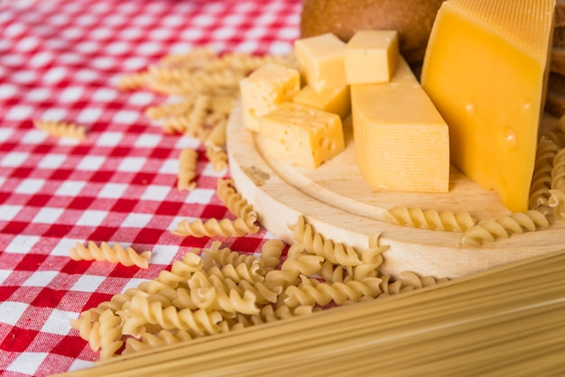 Cutting board with fresh cheese near scattered pasta on table
