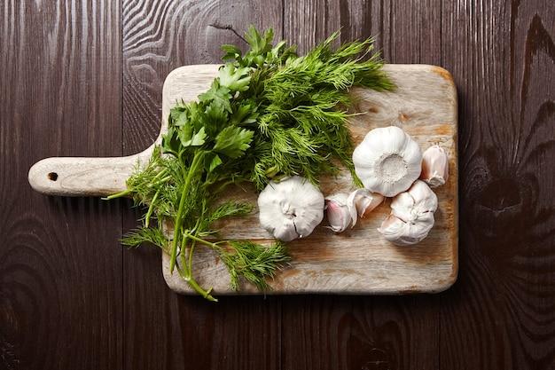新鮮なニンニクの頭とクローブ、グリーンディルとパセリの束が付いたまな板。調味料、上面図