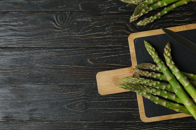 Cutting board with green asparagus on wooden