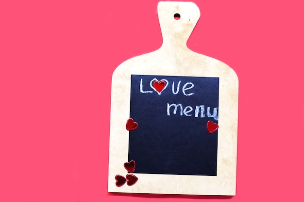 Cutting board with hearts and and the word menu on a red background
