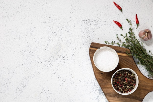 Cutting board with herbs on white concrete