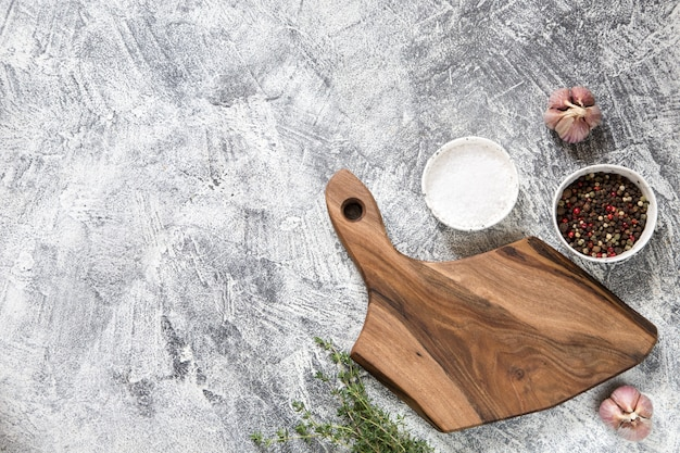 Cutting board with ingredients on grey concrete backdrop