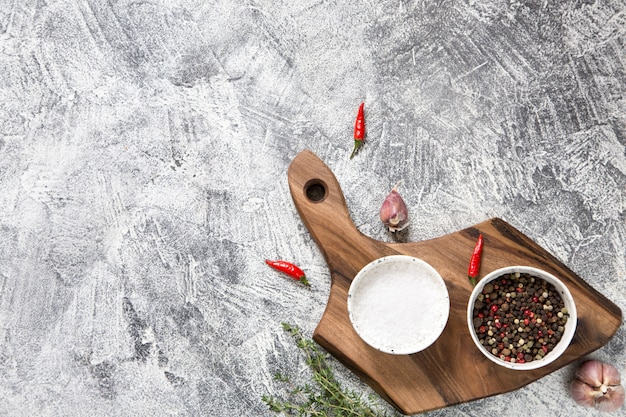 Cutting board with ingredients on white concrete