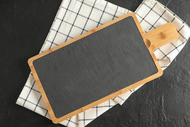 Cutting board with kitchen towel on black background, top view
