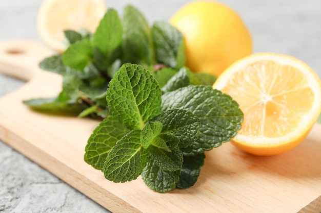 Cutting board with lemon and mint on grey, close up