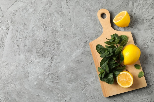 Cutting board with lemon and mint on grey, space for text