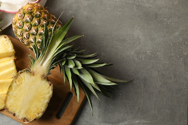 Cutting board with pineapples on grey background, top view