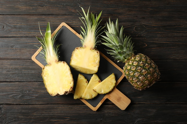 Cutting board with pineapples on wooden background, top view