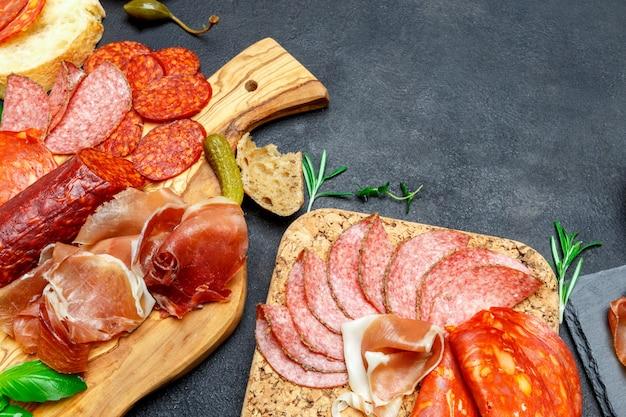 Разделочная доска с прошутто, салями, хлебными палочками и оливками